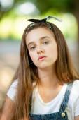 gyönyörű lány tinédzser farmer overálban egy szál fűvel a fogai között