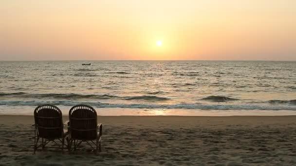 Dvě židle poblíž pobřeží v době západu slunce