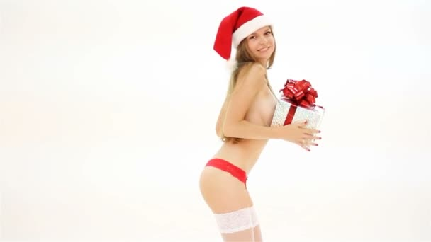 Beautiful nude christmas woman in santa hat with gift box dancing
