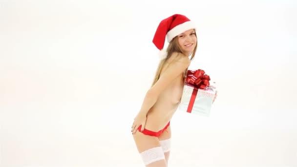 schöne nackte Weihnachtsfrau im Weihnachtsmann-Hut mit Geschenkbox tanzen