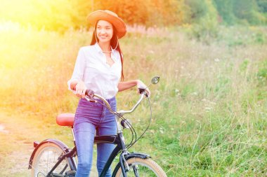 Woman with a black bicycle in a summer park or forest stock vector