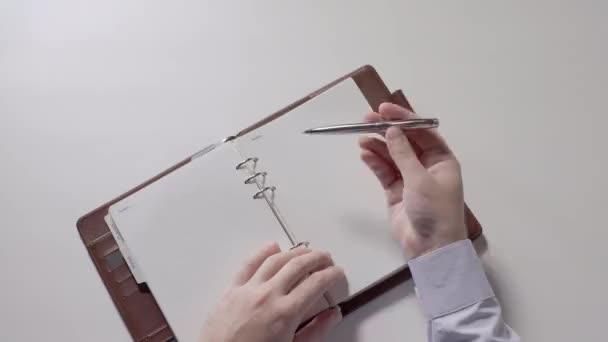 Muži se otáčí prázdné stránky spirála notebook. Ruce muže v detailním košile. V ruce kuličkové pero. Část 01