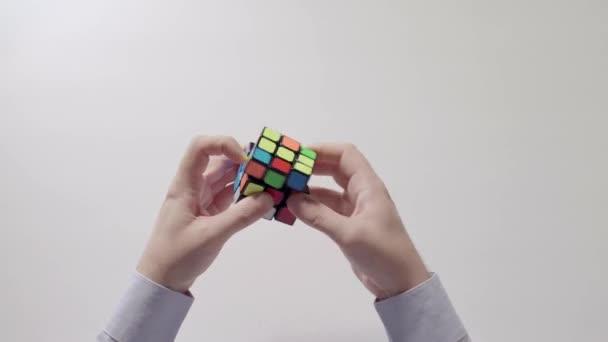 Businessmans hands solving puzzle. Puzzle cube, puzzle game, best-selling toys. Mans hands in a shirt closeup. Part 01.
