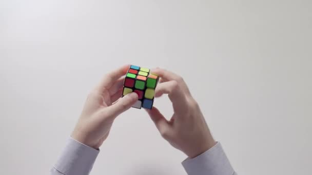 Businessmans hands solving puzzle. Puzzle cube, puzzle game, best-selling toys. Mans hands in a shirt closeup. Part 05. Recycled video.