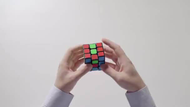 Businessmans hands solving puzzle. Puzzle cube, puzzle game, best-selling toys. Mans hands in a shirt closeup. Part 02. Speed up.