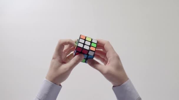 Podnikatel je ruce řešení puzzle. Puzzle kostka, puzzle hra, nejprodávanější hračky. Ruce muže v detailním košile. Část 01.