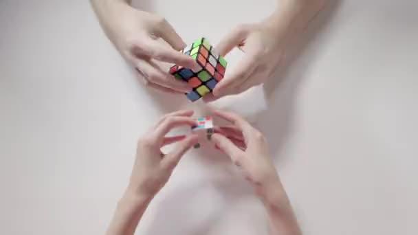Člověka a jeho ruce řešení Rubikova kostka puzzle. Puzzle kostka, puzzle hra, nejprodávanější hračky. Closeup ruce muže a dítěte. Část 02. Zrychlit.