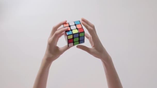 Ruce dítěte řešení Rubikova kostka puzzle. Puzzle kostka, puzzle hra, nejprodávanější hračky. Dětské ruce closeup. Část 01.