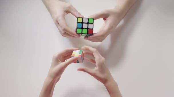 Mans and childs hands solving rubiks cube puzzle. Puzzle cube, puzzle game, best-selling toys. Mans and childs hands closeup. Part 01. Recycled video.
