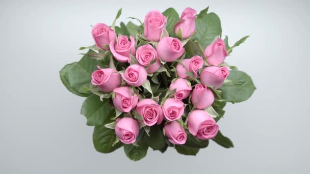 Womens hands locate a bouquet of pink roses on the table. 15