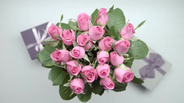 Bouquet of pink roses and two presents on the table. Static shot. 23