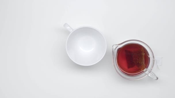 Empty chinese cup and glass kettle with tea bag on white background. Static shot. Tea ceremony. Part 26.