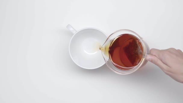 Ženských rukou nalít čaj v čínské šálky od Skleněná konvice tea bag na bílém pozadí. Čajový obřad. Část 27.