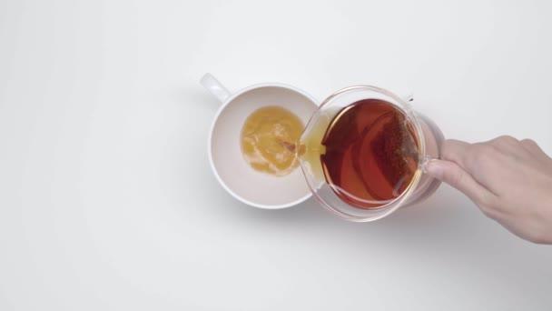 Ženských rukou nalít čaj čínských Cup od Skleněná konvice tea bag na bílém pozadí. Zpomalený pohyb. Čajový obřad. Část 31.