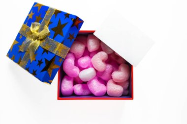 Gift or present box with filler with golden ribbon and greeting card on white background top view.