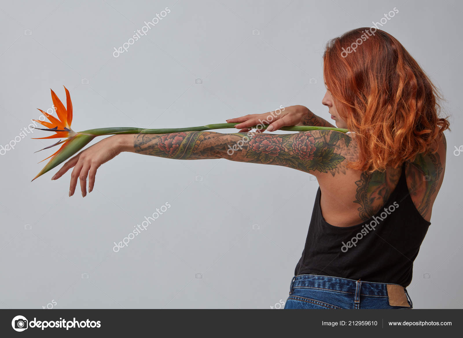 Sexy young girl with a tattoo holds an orange strelitzia flower around a  gray background with copy space. Layout for your ideas — Photo by ...
