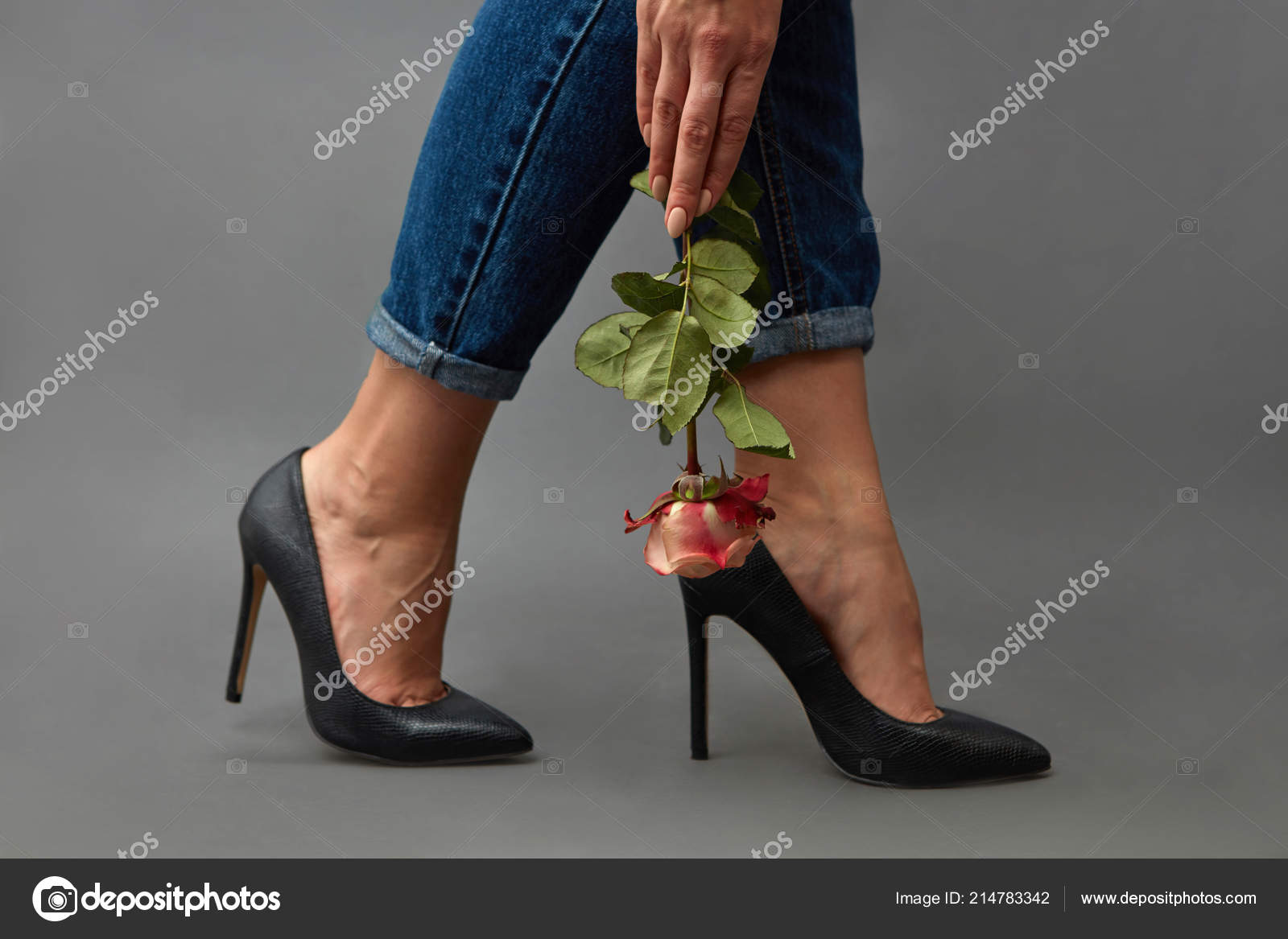 140a21a8aaf Legs of a woman in jeans and black high-heeled shoes next to a girl's hand  holds a pink rose around a dark background with space for text.