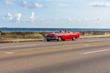 Red retro taxi car with tourists in Havana, Cuba. Captured on Malecon roadway in spring 2018