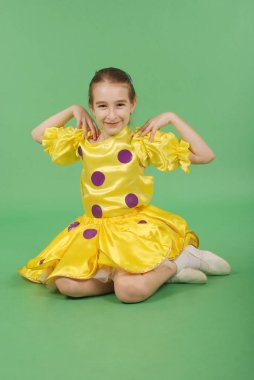 Pretty girl posing for the camera, in a yellow short dress. Isolated on green.