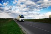Přijíždí bílý vůz na silnici a venkovské krajiny