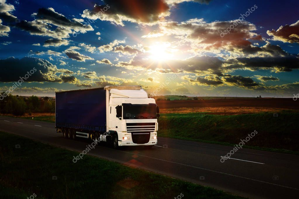 Arriving white truck on the road and rural landscape at sunset