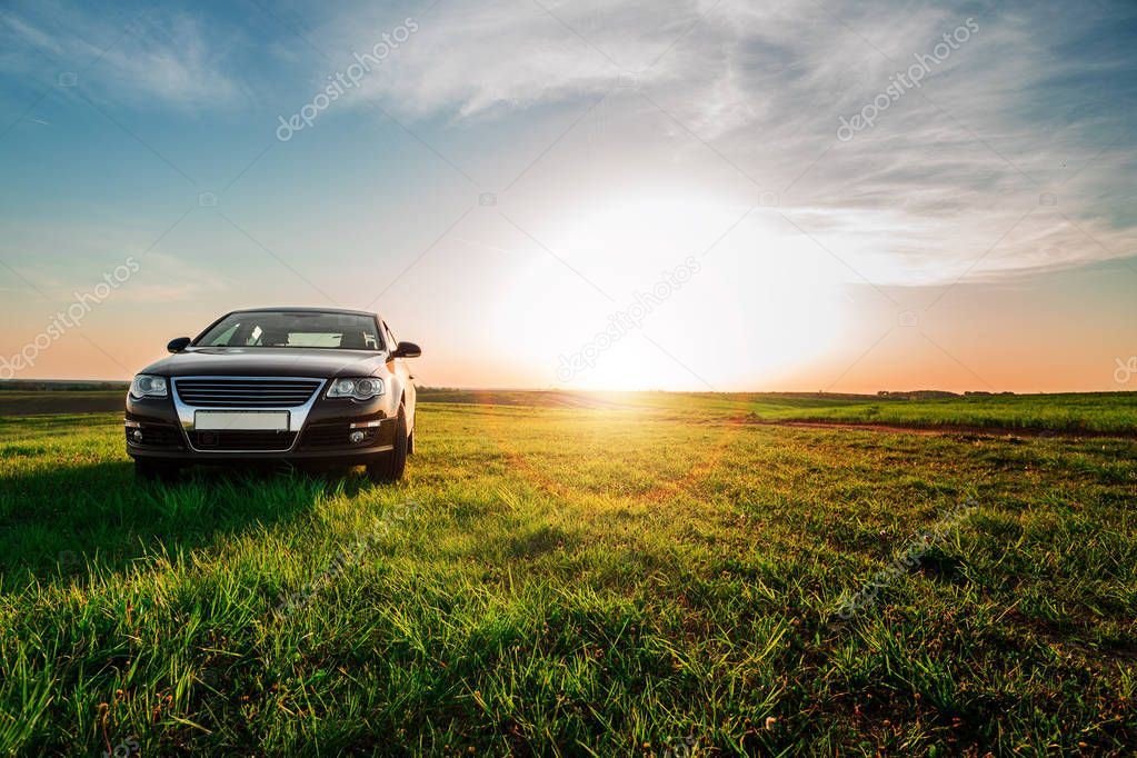 car on dirt road along green field on sunny day