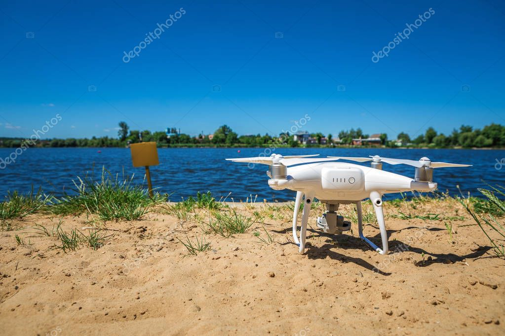 quadcopter drone flying in blue sky over the beach