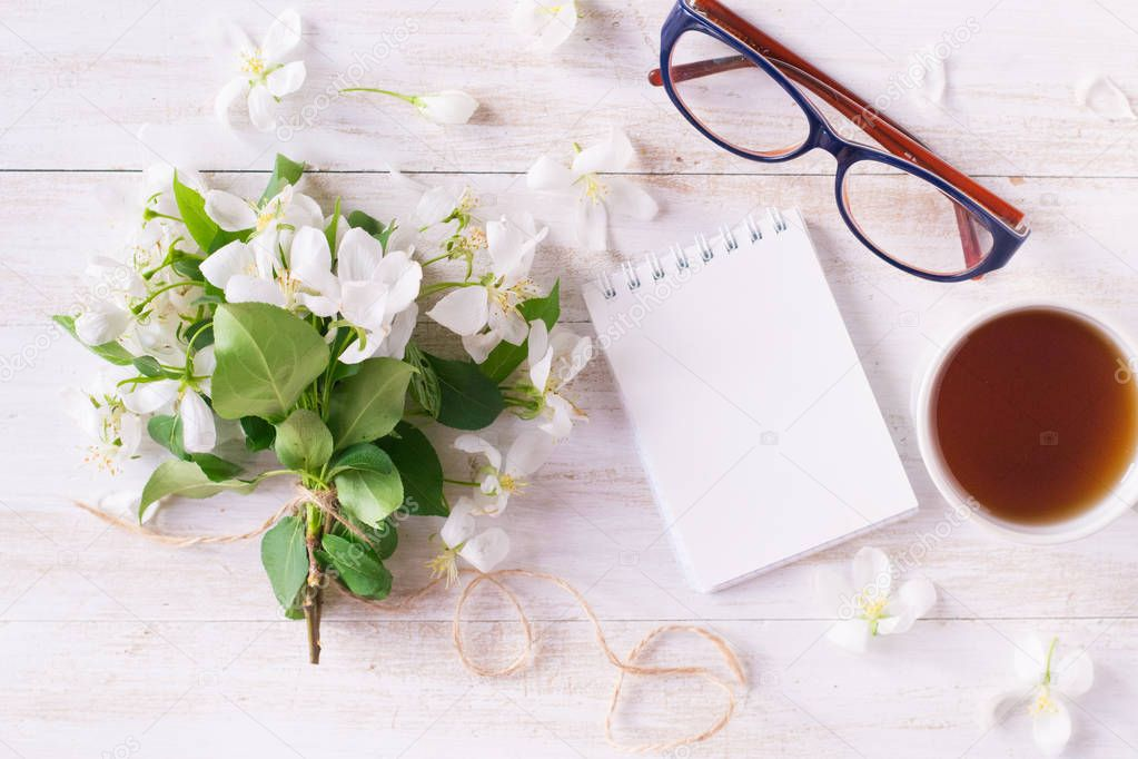 Flowers of apple tree, notebook, glasses ad cup of tea on wooden background