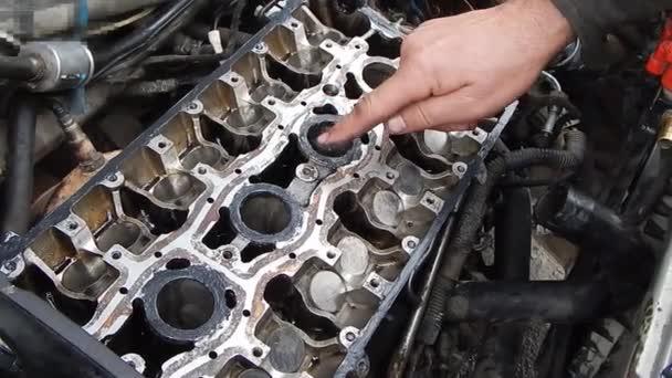Oprava spalovacího motoru s vnitřním spalováním. Montáž motoru. Aplikace těsnění na lůžku vačkové hřídele. Nanášení lepidla prstem.