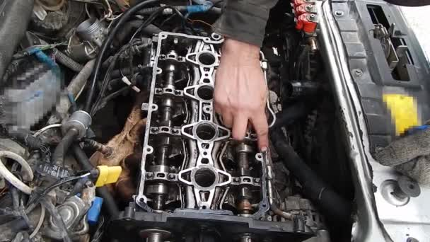 Repair of an internal combustion engine. Engine assembly. Sealant application on a camshaft bed. Applying sealant with your finger.