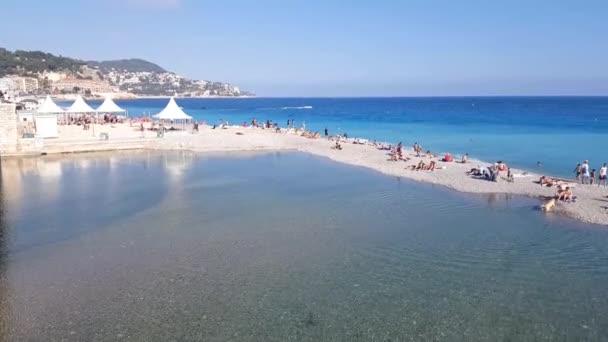 Nizza, Francia - 18 luglio 2018: Turisti godono il bel tempo in spiaggia a Nizza, Francia. La spiaggia e il viale lungomare, la Promenade des Anglais, sono pieno quasi tutto lanno.