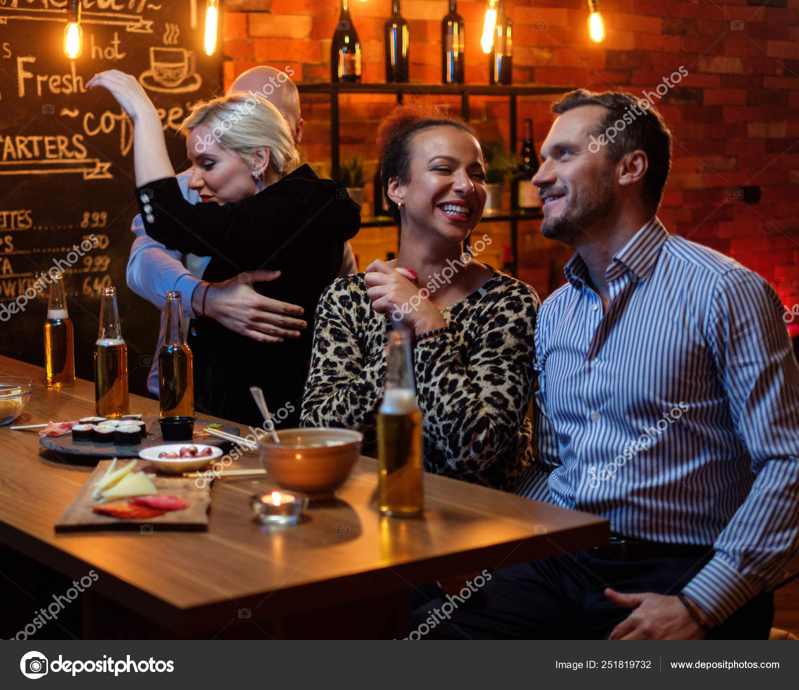 Group Of Friends Watching Tv In A Cafe Behind Bar Counter Stock Photo C Nejron 251819732