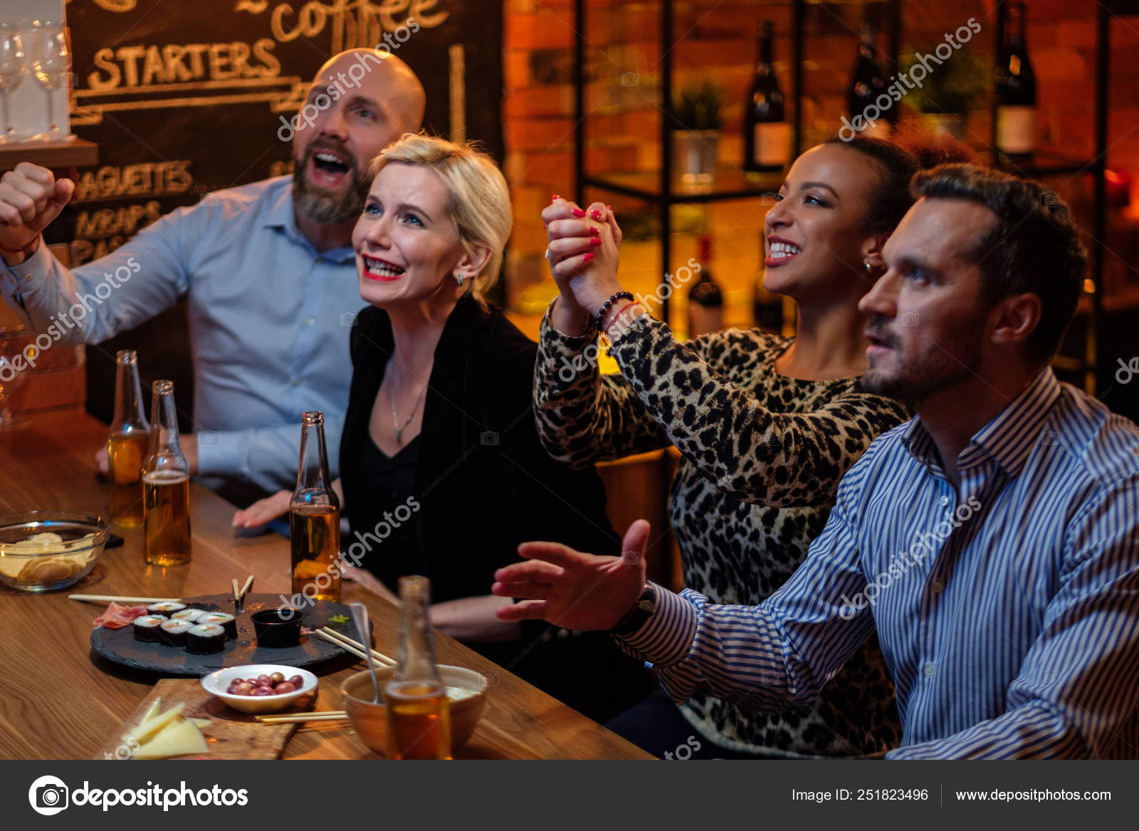Group Of Friends Watching Tv In A Cafe Behind Bar Counter Stock Photo C Nejron 251823496