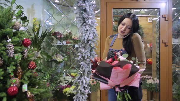 Ženské květinářství s kyticí v její ruce komunikuje se zákazníkem nebo dodavatelem telefonicky, popisuje nebo přijímá objednávky.