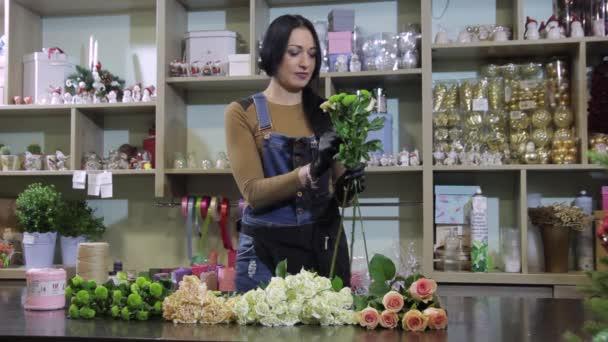 Ženské květinářství vytvoří kytice čerstvých květin v úložišti na pozadí Windows obchod s květinovou výzdobu.