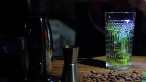 Barkeeper macht einen frischen und kalten süßen Mojito-Sommercocktail auf der Theke