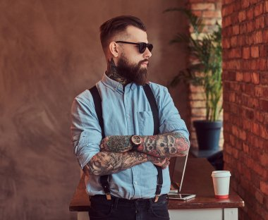 Old-fashioned tattooed hipster wearing a shirt and suspenders, in a sunglasses, standing with crossed arms near a desk with a laptop, looking out the window in an office with loft interior.