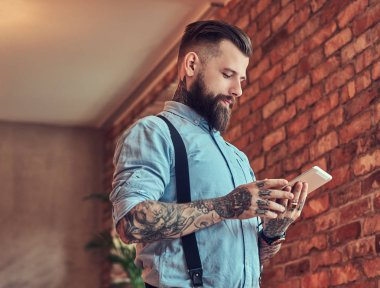 Old-fashioned tattooed hipster wearing a shirt and suspenders, in a sunglasses, using a tablet while standing near a desk in an office with a loft interior.
