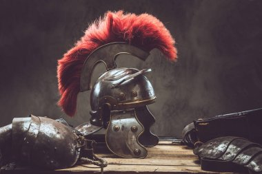 Complete combat equipment of the ancient Greek warrior lie on a box of wooden boards. Isolated on a dark background.