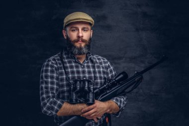 Portrait of a bearded hunter traveler in a fleece shirt and hat holds rifle with a sight and binoculars. Isolated on a dark background.