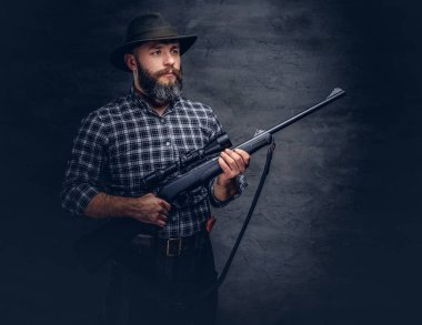 Handsome bearded hunter traveler in a fleece shirt and hat holds rifle with a sight. Isolated on a dark background.