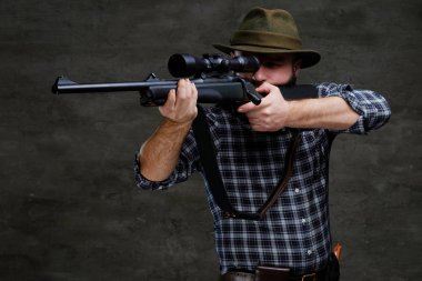 Hunter aiming a rifle in sight while preparing to make an accurate shot at the prey. Isolated on a dark background.