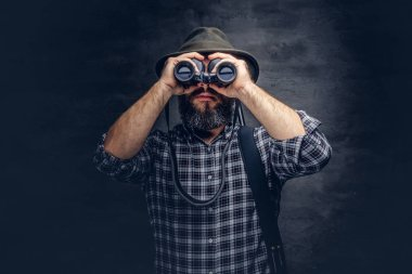 Portrait of a bearded hunter traveler tries to find prey while looking through binoculars. Isolated on a dark background.