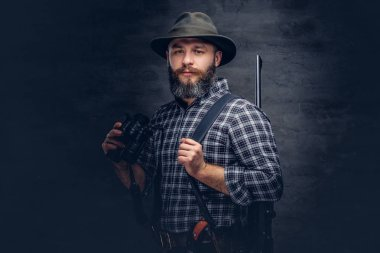 Portrait of a bearded hunter in a fleece shirt and hat holds binoculars while standing with a rifle behind his back. Isolated on a dark background.