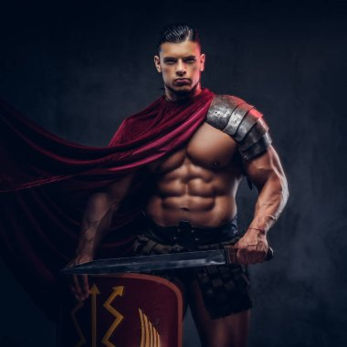 Brutal ancient Greece warrior with a muscular body in battle uniforms posing on a dark background.