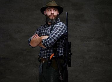 Portrait of a bearded hunter in a fleece shirt and hat standing with a rifle behind his back. Isolated on a dark background.