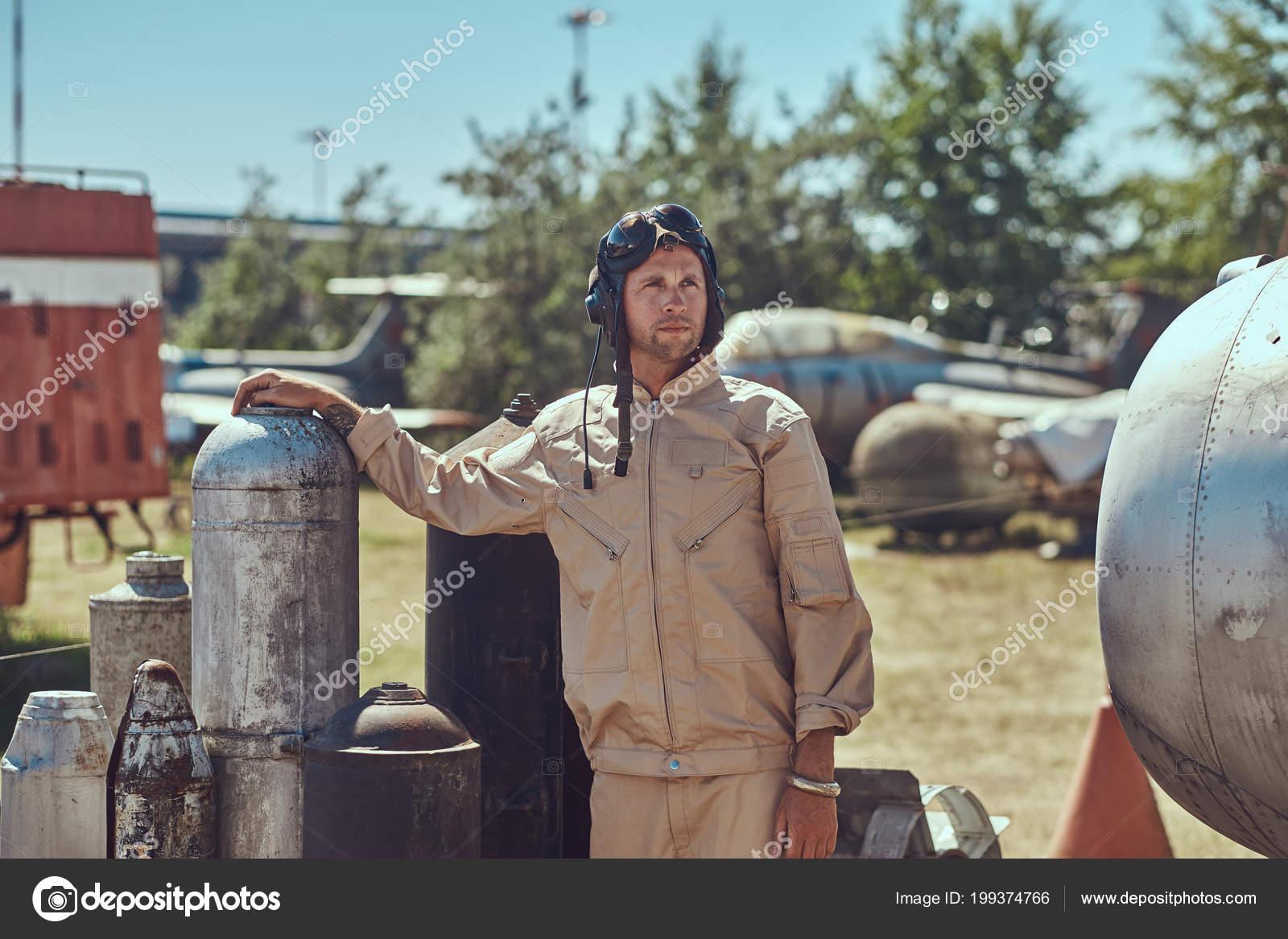 651e397cd4 Ritratto di un pilota in uniforme e volante casco vicino combattimento  bombe per un bombardiere in un museo a cielo aperto– immagine stock