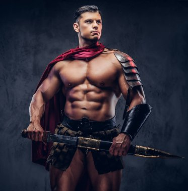 Brutal ancient Greek warrior with a muscular body in battle equipment posing on a dark background.
