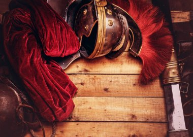 Complete combat equipment of the ancient Greek warrior on a wooden boards background.