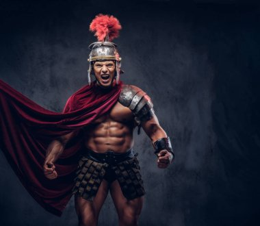 Brutal ancient Greece warrior with a muscular body in battle uniforms screams in battle agony on a dark background.